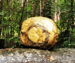Goldener, bemalter Stein.