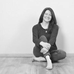 Ayurveda Coach Christiane sitzt in Jeans ganz lässig auf dem Boden im Yogaraum in Büdingen.