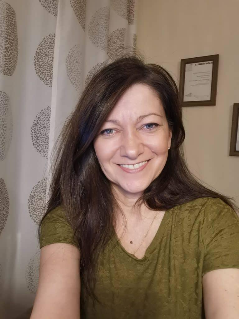Christiane sitzt in ihrem Büro am Schreibtisch
